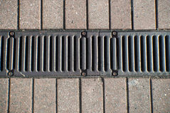 Drain in the middle of a paved footpath Stock Image