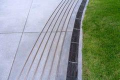 Drain ou fossé de l'eau de courbe sur la route Les goutti?res vidangent la grille, couverture de drain photo libre de droits