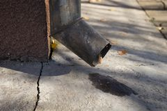 Drain pipe on the corner of the house with a small puddle.  royalty free stock images