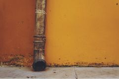 Drain pipe in front of the yellow wall stock image