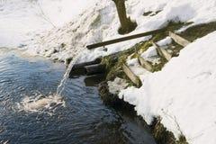 Drain in the river, thaw, snowbreak, drainage Stock Image
