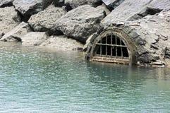 Drain sewage contaminating water Stock Image