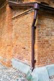 Drain sur le mur superficiel par les agents de brique rouge Photos stock