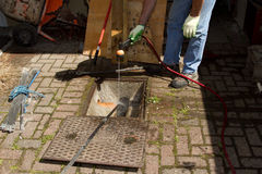 Drain unblocking. A man spraying water into a blocked drain with the cover off and rods extending into the drain Royalty Free Stock Photography