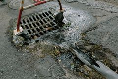 Drain the water into the sewer. Photo in the daytime Royalty Free Stock Photos