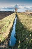 Drainage channel running alongside a ploughed field Stock Images
