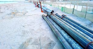 Drainage pipe laying surrounded by litter on sandy beach