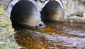 Drainage pipes made of concrete under the road, to divert water during  spring flood. A strong stream of  forest stream, after