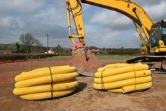 Drainage Piping. Two rolls of yellow plastic drainage piping on a building site, with part of an excavator to the rear Royalty Free Stock Images