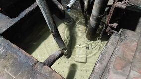 Drainage pit for groundwater. Monotonous sound of dripping water