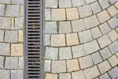 Drainage on stone paved street Royalty Free Stock Photos