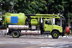 Drainage truck. Green drainage truck through the street in the moring Stock Photo