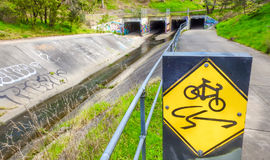 Drainage tunnels and warning sign. Drainage tunnels and bike path warning sign Stock Image