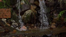 Drainage water streams fall among the wet stones and form splashes.