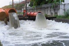 Drainagepijp met water die in de rivier stromen stock fotografie
