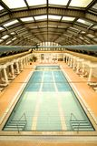 Drained indoor swimming pool with sun loungers Royalty Free Stock Images