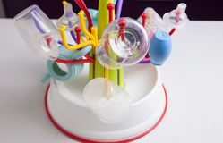 Drainer full of baby plastic tableware objects Stock Photos