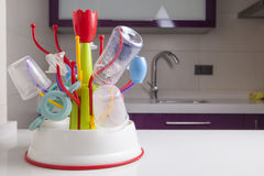 Drainer full of baby plastic tableware objects. Baby drainer full of plastic tableware objects as baby bottles, nasal aspirator, milk bowls, teats and others Royalty Free Stock Photography