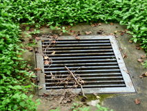 Draining hole surrounded by grass. Water Outflow. Raining hole Royalty Free Stock Photography
