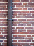 Drainpipe against brick wall Stock Photography