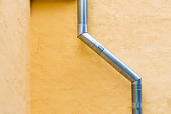 Drainpipe against yellow wall Stock Photography