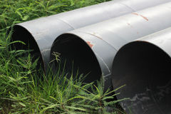 Drains are placed outdoors, waiting for construction, with weeds Royalty Free Stock Photo