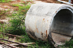 Drains are placed outdoors, waiting for construction, with weeds Stock Images
