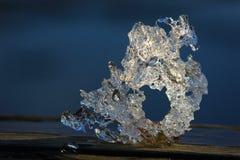Drake-som stora bitar av is som fångas i en sjö i vår mot en strand arkivbild
