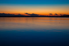 Drakehuvudmoln på solnedgångsjön Royaltyfri Foto