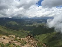 Drakensberg. High up on a cliff over looking a green valley with blue skys and heavy clouds Stock Photography