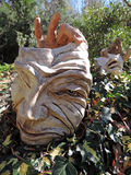 Drama Face and hands sculpture in garden. Drama Face and hands sculpture lying on a bed of ivy in the garden Royalty Free Stock Photo