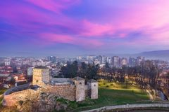 Drama in the sky, ancient fortress and city lights during foggy blue hour. Colorful, purple sunset and fluffy, sunlit magenta clouds over blue hour Pirot stock photos