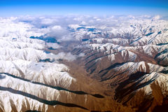 Dramatic Aerial view of snow-covered mountains. Aerial view of snow-covered mountains under cloudy blue sky Stock Photos