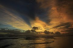 Dramatic Afternoon Sky Mystery. The dramatic afternoon sky on the beach, the sky burning with the tidal waves brings a restless atmosphere between beauty and Royalty Free Stock Photography
