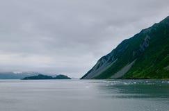 Dramatic Alaskan seascape and mountainous terrain. A dramatic alaskan seascape with floating ice and steep, mountainous terrain under a stormy sky Stock Photos