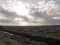 Dramatic autumn grey stormy clouds with sun beams over coastal g Stock Photography
