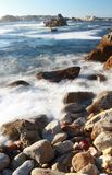 Waves crashing on rocky coastline of Asilomar State Marine Reserve in Pacific Grove, near 17 mile drive and Monterey, California. Dramatic background of ocean at Stock Image