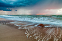 Dramatic Baltic sunset. Dramatic colorful sunset with low rainy clouds on Baltic sea in Pavilosta, Latvia Stock Images
