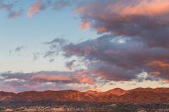 Beautiful sunset casts purple and orange colors on clouds and mountains over a neighborhood in Tesuque, near Santa Fe, New Mexico. Dramatic sunset over the stock photos