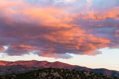 Beautiful sunset casts purple and orange colors on clouds and mountains near Santa Fe, New Mexico royalty free stock photos