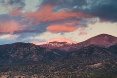 Dramatic, beautiful sunset illuminates the peak of Santa Fe Baldy over a neighborhood in Santa Fe, New Mexico royalty free stock photography