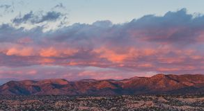 Dramatic, beautiful sunset casts purple and orange colors and hues on clouds and mountains stock image