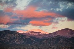 Dramatic, beautiful sunset casts purple and orange colors and hues on clouds and a snow-capped peak near Santa Fe, New Mexico stock photography