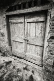 Dramatic black and white old wooden door. A wide shot of a wooden door from outside an old structure Stock Images