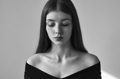 Dramatic black and white portrait of a beautiful lonely girl with freckles isolated on a white background in studio shot stock images