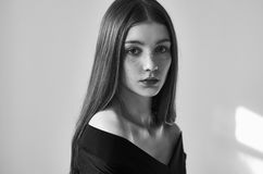 Dramatic black and white portrait of a beautiful lonely girl with freckles isolated on a white background in studio shot royalty free stock photography