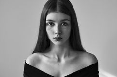 Dramatic black and white portrait of a beautiful lonely girl with freckles isolated on a white background in studio shot royalty free stock photo