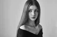 Dramatic black and white portrait of a beautiful lonely girl with freckles on a white background in studio shot. Dramatic black and white portrait of a beautiful royalty free stock image
