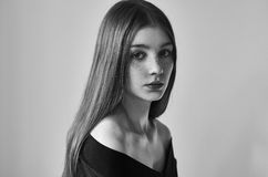 Dramatic black and white portrait of a beautiful lonely girl with freckles on a white background in studio shot stock photography