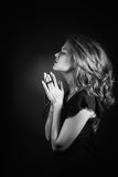 Dramatic black and white portrait of a woman  praying or thinking emerging from a black background Royalty Free Stock Photos